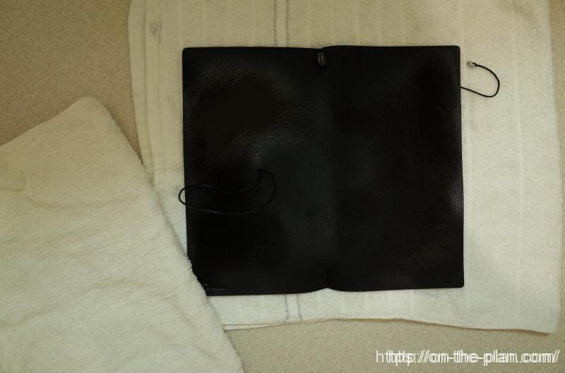 黒のトラベラーズノートが、かなり汚れてきたので、おもいきって洗濯。タオルに挟んで水気をしっかりとっています。